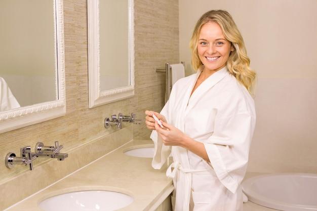 Loira bonita segurando teste de gravidez positivo no banheiro