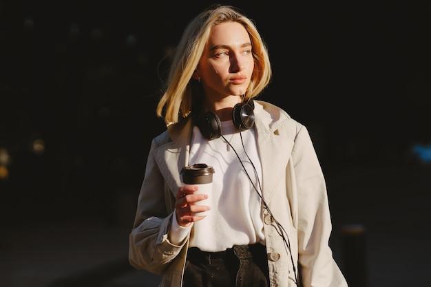 Loira caminha na cidade de verão com uma xícara de café