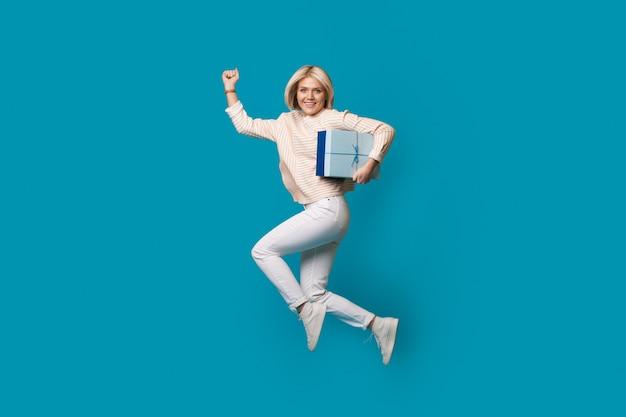 Loira caucasiana com uma caixa de presente está pulando na parede azul de um estúdio gesticulando para correr