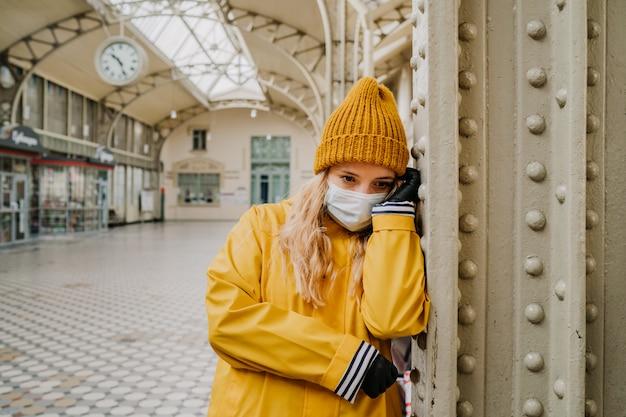 Loira chateada usando máscara médica e luvas de proteção, vestindo blusão amarelo e boné em pé na estação de trem vazia. ela ouviu más notícias sobre a pandemia da capa 19. conceito de problema de coronavírus.
