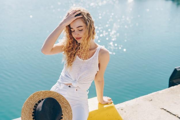 Loira cobriu os olhos do calor do sol e se senta no parapeito contra o mar