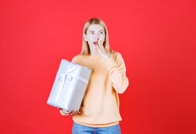Loira colocando a mão perto da boca enquanto segura a caixa de presente em frente à parede vermelha