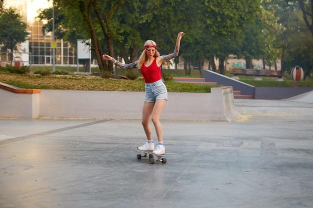 Loira com braços tatuados vestida com uma camiseta vermelha e shorts jeans com uma bandana de tricô na cabeça, de óculos vermelhos, praticando longboarding no skate park, parece concentrada com as mãos para cima.