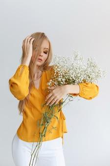 Loira com cabelo comprido saudável com flores delicadas e maquiagem em um fundo cinza. poster. beleza