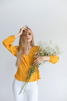 Loira com cabelo saudável e maquiagem brilhante com flores brancas no estúdio em um fundo cinza.