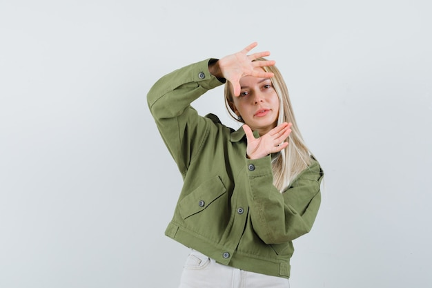 Loira com jaqueta, calça fazendo gesto de quadro e parecendo confiante, vista frontal.