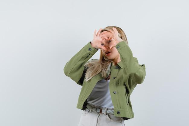 Loira com jaqueta, calça mostrando um gesto de coração e olhando bonita, vista frontal.