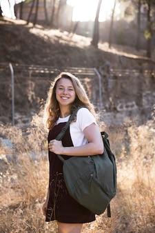 Loira com mochila sorrindo e olhando para a câmera