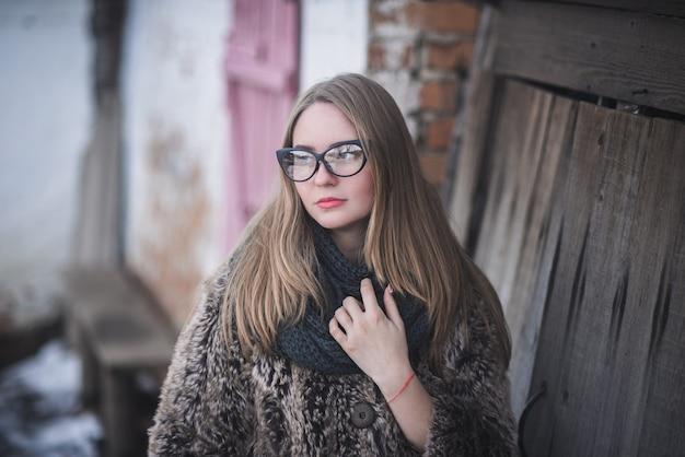 Loira com óculos de gato e um casaco de pele artificial posando