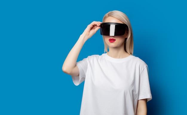 Loira com óculos futuristas de realidade virtual no espaço azul