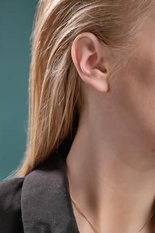 Loira com piercing nas orelhas em close-up de jaqueta preta