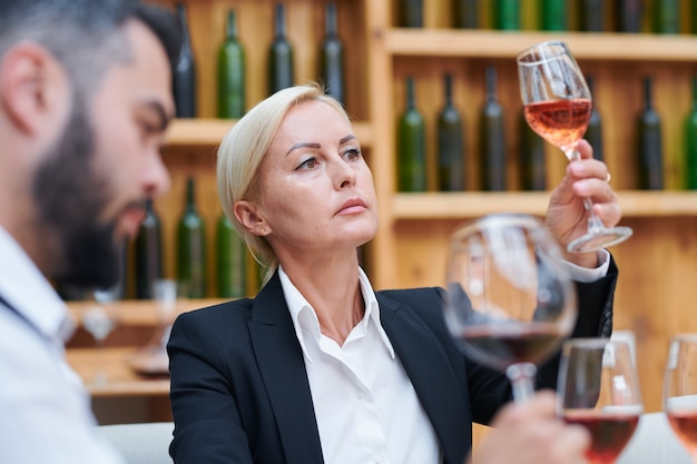 Loira confiante sommelier feminina ou cavista olhando para a cor de um vinho em um copo de vinho no trabalho na adega