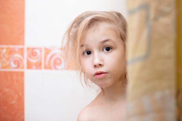 Loira criança no banheiro debaixo do chuveiro.