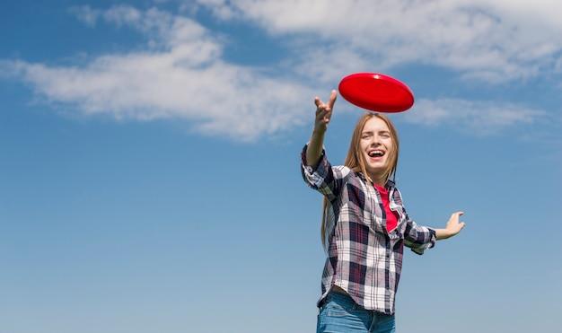 Loira de ângulo baixo, jogando um frisbee vermelho