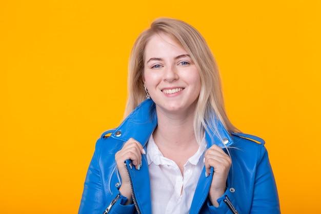 Loira de boa jovem positiva na jaqueta de couro azul, posando sobre uma superfície amarela. jovem feliz