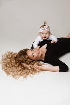 Loira de cabelos compridos em um macacão preto deitada e sorrindo com uma filha abraçando-a