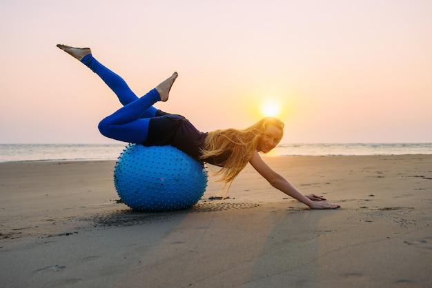 Loira de cabelos compridos está envolvida em pilates em uma bola de treinamento na praia durante o pôr do sol