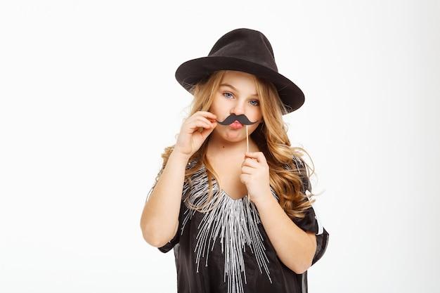 Loira de cabelos longos, posando com máscara de bigode no palito.