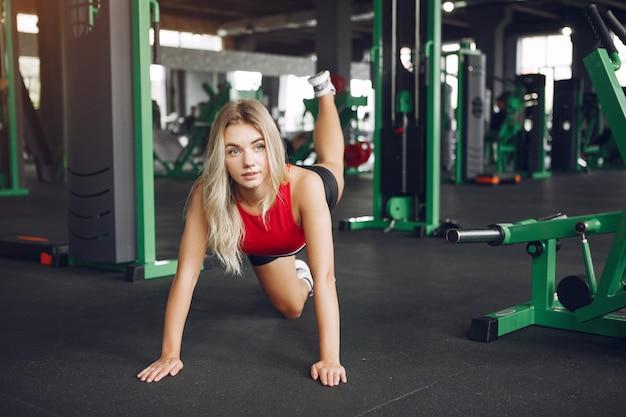 Loira de esportes em um sportswear descansar em uma academia