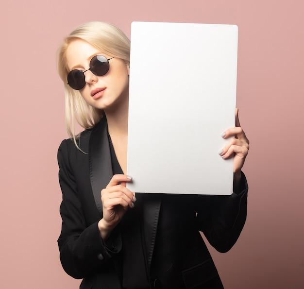 Loira de estilo com blazer e óculos escuros com papel no fundo rosa