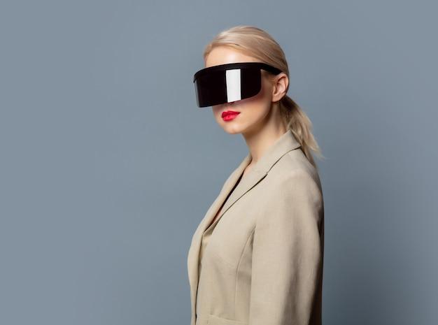 Loira de estilo com óculos futuristas de realidade virtual no espaço cinza