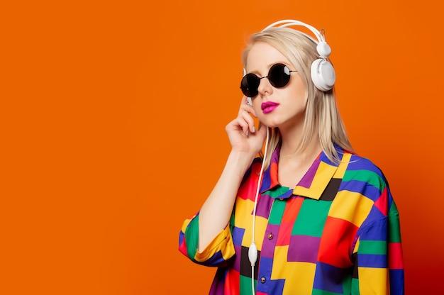 Loira de estilo com roupas dos anos 90 com fones de ouvido na cor laranja