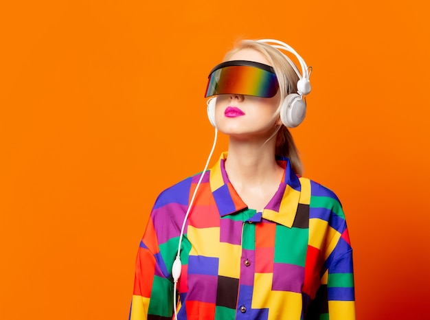 Loira de estilo com roupas dos anos 90 com óculos de realidade virtual e fones de ouvido laranja