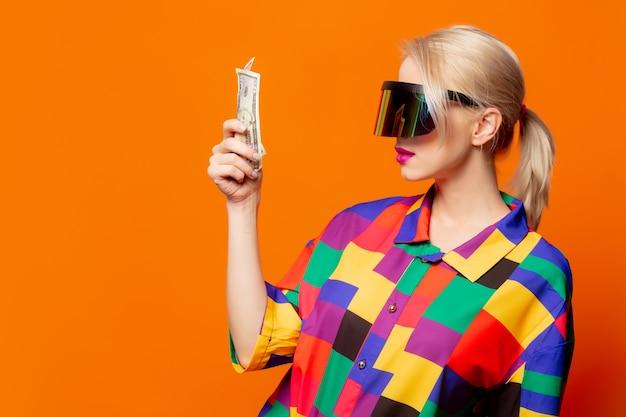 Loira de estilo com roupas dos anos 90 e óculos de realidade virtual com dinheiro em laranja