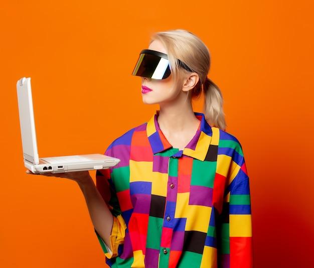 Loira de estilo em roupas dos anos 90 com notebook e óculos vr laranja