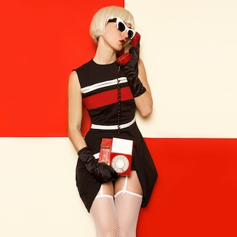 Loira de estilo retrô sexy cabaré em roupas vintage e telefone retrô. moda minimalista. stripe design