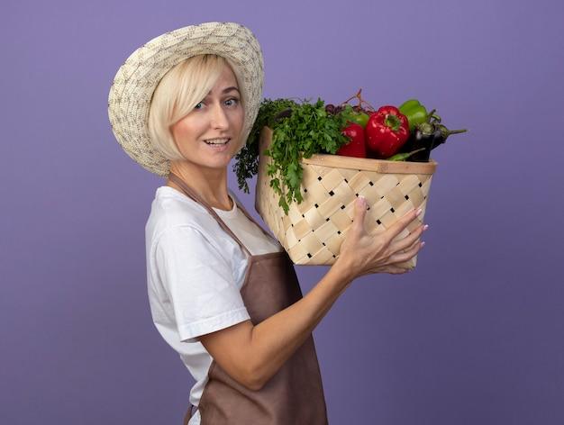 Loira de meia-idade, alegre, jardineira, de uniforme, usando um chapéu