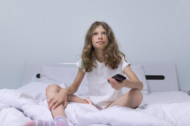 Loira de menina bonita criança de manhã sentada na cama branca com o controle remoto da tv.