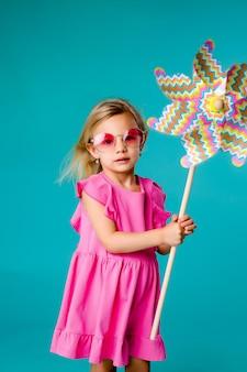 Loira de menina criança sorrindo em óculos de sol em um vestido rosa, segurando um moinho de vento sobre um fundo azul de isolar