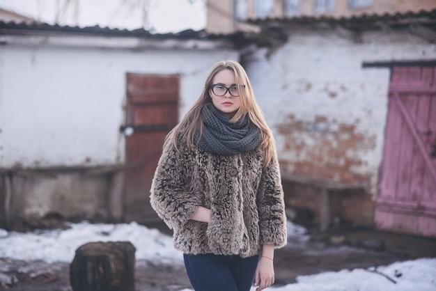 Loira de menina de óculos com olhos de gato em um casaco de pele sintética artificial posando.