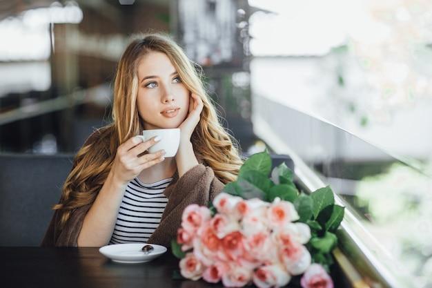 Loira de mulher jovem bonita em roupas casuais, descansando e bebendo café em um café do terraço de verão.