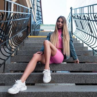 Loira de mulher jovem e bonita europeia com uma jaqueta jeans na moda shorts rosa em um top rosa com tênis branco senta-se em uma escada de pedra vintage ao ar livre num dia de verão. garota urbana relaxando na cidade
