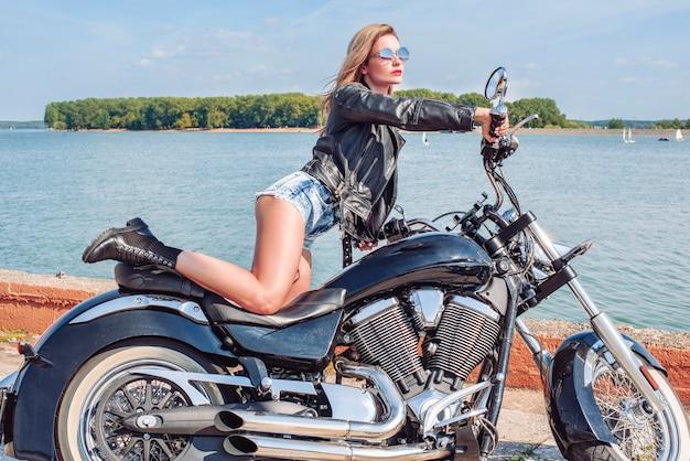 Loira deslumbrante e elegante em uma jaqueta de couro preta e shorts jeans posa perto de uma enorme motocicleta. o conceito de automobilismo, turismo, estilo de moda. mídia mista