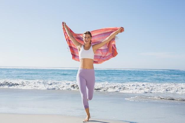 Loira desportiva em pé na praia com um cachecol