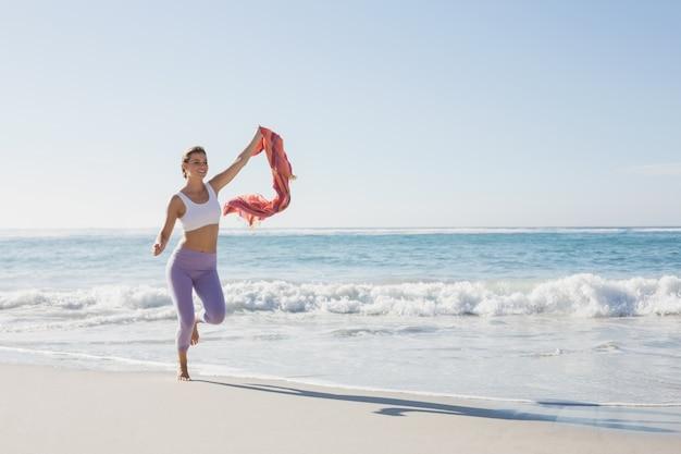 Loira desportiva jogging na praia com um lenço