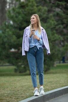 Loira elegante alegre segurando café ao ar livre. jovem mulher bebendo café nas ruas da cidade.