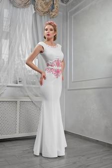 Loira elegante, bonita, elegante da moda em um longo dre branco