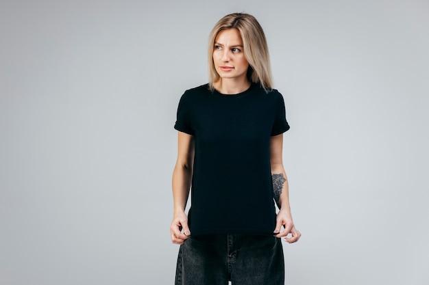 Loira elegante com camiseta preta posando