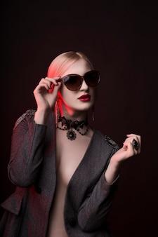 Loira elegante de óculos com maquiagem brilhante em estúdio