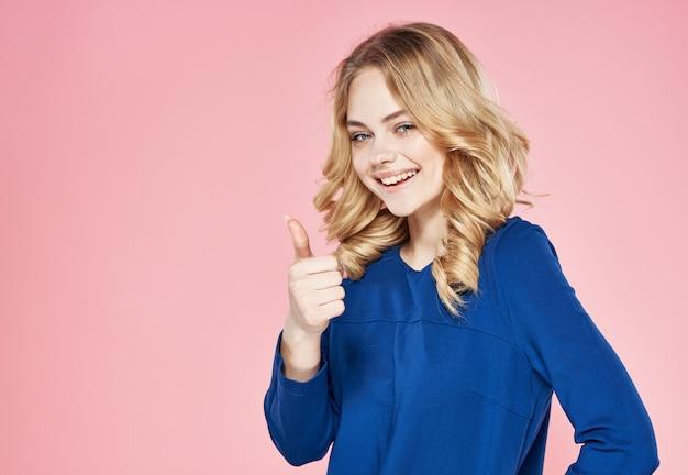 Loira elegante em um vestido azul emoção estilo de vida fundo rosa