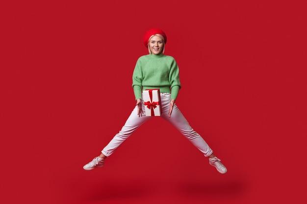 Loira elegante está pulando em uma parede vermelha segurando uma caixa de presentes e usando um chapéu sorrindo para a câmera