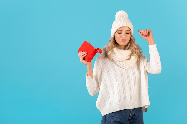 Loira elegante sorrindo linda jovem segurando um alto-falante sem fio, ouvindo música, dançando feliz vestindo um suéter branco e um chapéu de malha de inverno estilo posar isolado na parede azul