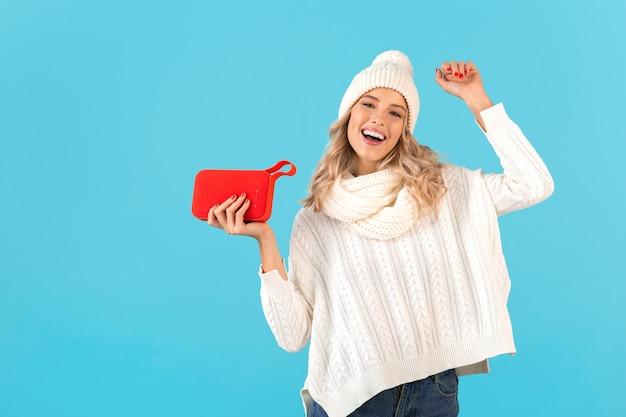 Loira elegante sorrindo linda jovem segurando um alto-falante sem fio, ouvindo música, dançando feliz vestindo um suéter branco e um chapéu de malha