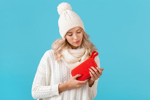Loira elegante sorrindo linda jovem segurando um alto-falante sem fio, ouvindo música, feliz vestindo um suéter branco e um chapéu de malha estilo inverno