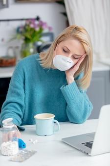 Loira em máscara com copo de bebida, termômetro e computador portátil na cozinha