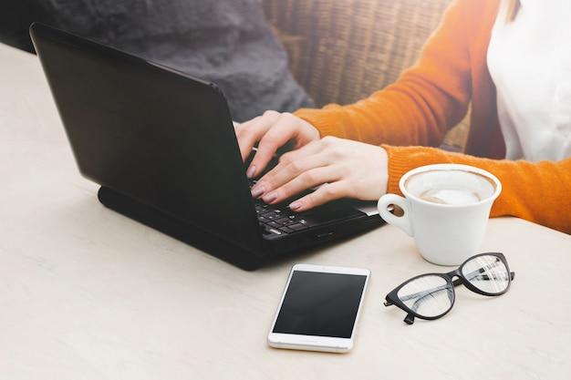 Loira em um café com um laptop e café. freelancer de jovem garota trabalhando em um laptop